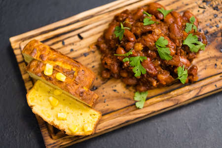 Native American cuisine. Top view of Boston baked beans and cornbread on rustic wooden board. Stock fotó