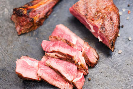Steakhouse menu. Cowboy steak. Top view closeup of sliced grilled beef meat and bone.