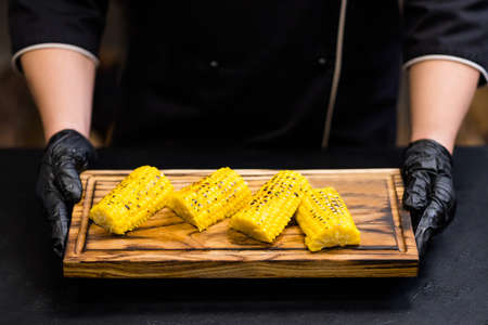 Professional catering service. Cropped shot of chef holding wooden board with baked sweet Bonduelle corn on cob pieces.