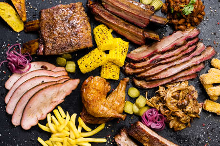 Steakhouse menu. Top view of sliced smoked meat assortment, French fries and vegetable dishes.
