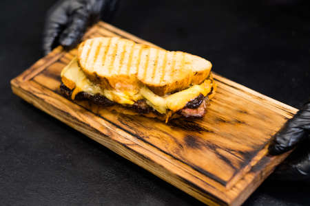 Grill restaurant. Closeup of smoked beef brisket sandwich with rustic bread and cheddar cheese on wooden board. Zdjęcie Seryjne