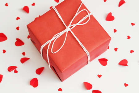 Romantic surprise. Top view of red paper wrapped gift box on heart pattern white background.