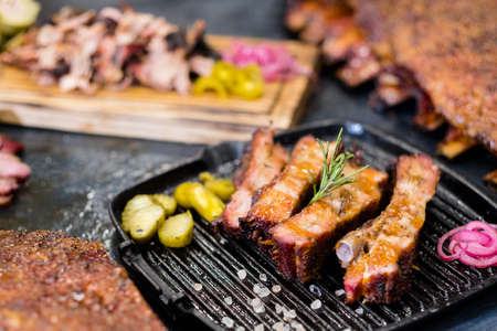 Grill restaurant. Closeup of smoked pork ribs on griddle pan. Pulled pork and ribs in background. Stock Photo