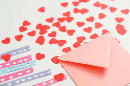 Handmade greeting card. Closeup of pink envelope, love theme stencil plates and cutout paper hearts on white background. Reklamní fotografie