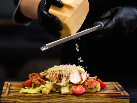 Traditional Italian recipe. Cropped shot of chef grating Parmesan cheese into Caesar salad with smoked chicken fillet and bacon.