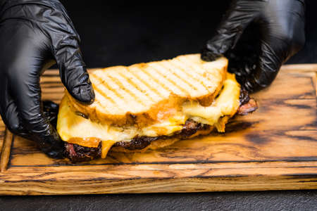 Professional catering. Closeup of chef hands serving smoked beef brisket sandwich on wooden board.