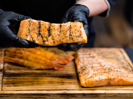 Seafood recipe. Chef in black cooking gloves holding seasoned smoked salmon fillet over langoustines on wooden board.