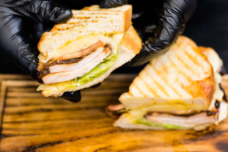 Grill restaurant. Closeup of chef hands holding a half of smoked turkey breast sandwich over wooden board.