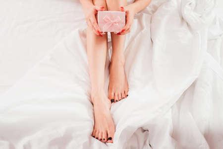 Huidverzorgingsproducten. Bijgesneden bovenaanzicht van vrouw met benen zittend op bed met roze geschenkdoos.