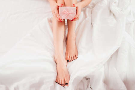 Skin beauty care products. Cropped top view of woman with bare legs sitting on bed with pink gift box.