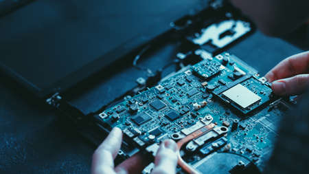Microelectronics technology. Hardware development. Technician checking motherboard.