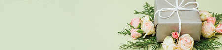 Holiday surprise. Special occasion congratulation. Gift box floral decor on sage green background. Reklamní fotografie