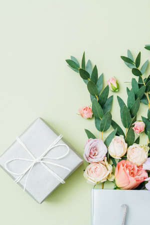 Gift delivery. Birthday greeting. Flowers in shopping bag wrapped present on green toned background.