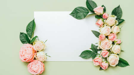 White blank paper. Mother day greeting. Pink roses decorative composition on sage green background.