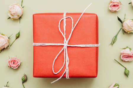 Holiday surprise. Anniversary greeting. Red gift box on rose floral pattern background.