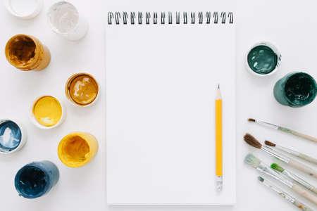 Empty notepad. Creative leisure hobby. Gouache pencil paintbrush set on white background.
