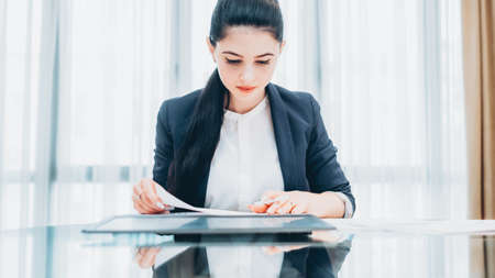 Woman in business. Portrait of successful female leader working at modern office, reviewing report.