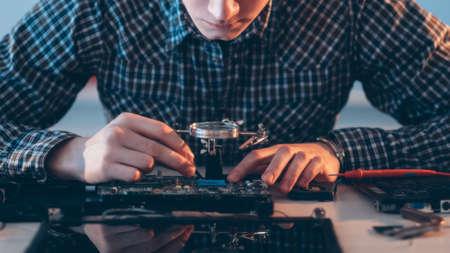 Electronic engineering. Hardware maintenance. Male technician testing disassembled laptop.