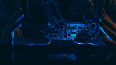 Microelectronics technology. Hardware diagnostics. Engineer examining motherboard.