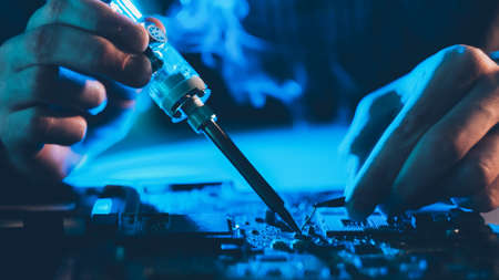 Computer engineering. Hardware maintenance service. Male technician soldering motherboard. Banque d'images
