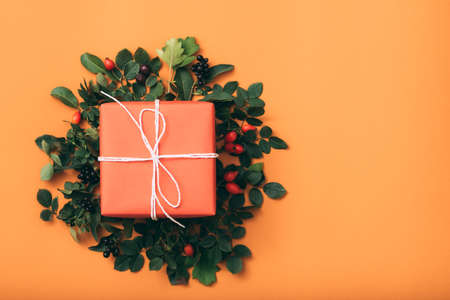 Holiday present. Anniversary greeting. Gift box. Floral composition Orange background