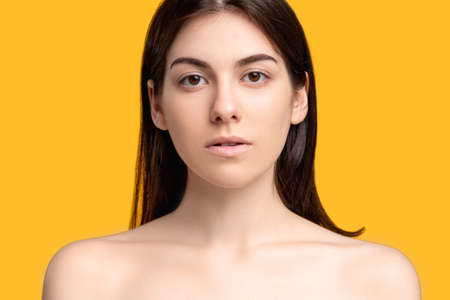 Aesthetic cosmetology. Plastic surgery. Portrait of woman with fresh pure perfect face skin bare shoulders isolated on orange copy space. Feminine beauty wellness. Banco de Imagens