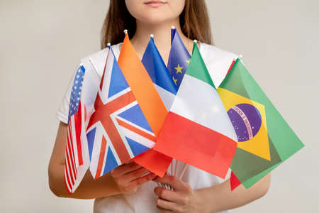 World community. Global organization. Woman holding international flags isolated on blur light background. Political convention. United nations. Governmental conference. General council.