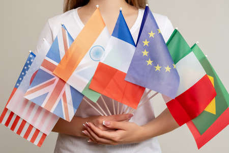 World peace. Global unity. Woman holding international flags isolated on light background. Political convention. Political meeting. Governmental conference. General council. Multinational diplomacy.