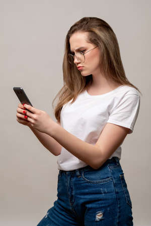 Social media anxiety. Disturbing news. Concerned woman in glasses reading feed on phone isolated on gray background. Mobile technology. Internet stress.