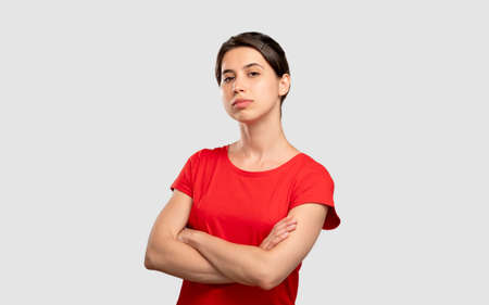 Dislike gesture. Bad job. Sad woman in red t-shirt showing thumb down looking at camera. Isolated on neutral. Disapproval sign. Unhealthy habit. Advertising background