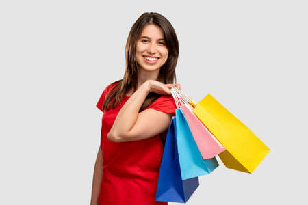Black friday. Sale and discount. Happy woman holding colorful bags looking at camera isolated on neutral copy space. Cyber monday. Shopaholic lifestyle. Holiday gifts 스톡 콘텐츠