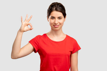 Ok gesture. Approval sign. Happy young in red t-shirt woman showing fine looking at camera isolated on neutral. Good job. Positive lifestyle. Advertising background
