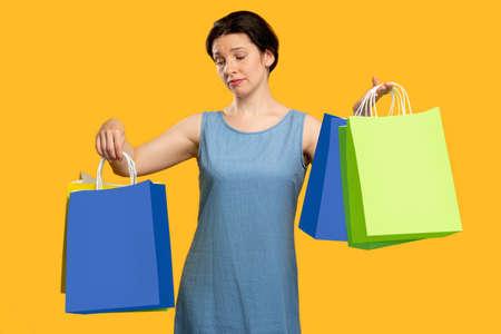 """购物上瘾。失望的情绪。悲伤的女人看着购物袋。孤立的橙色。购物狂的生活方式。销售和折扣。""""黑色星期五""""。网络星期一"""