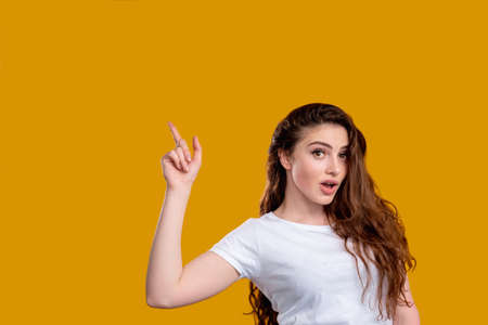 Surprised woman portrait. Aha moment. Shocked lady with open mouth pointing up at copy space isolated on orange wall. Eureka effect. Found solution. Insight idea. Advertising background. Stock Photo