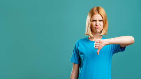 Dislike gesture. Bad idea. Disgusted blonde woman in blue t-shirt showing thumb down isolated on teal copy space advertising background. Loser shame. Not cool.