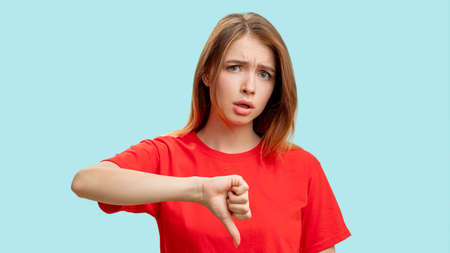 Dislike gesture. Negative answer. Portrait of annoyed skeptic woman in red t-shirt criticizing showing thumb down isolated on blue background. Loser shame. Mistake failure blame. Stock fotó