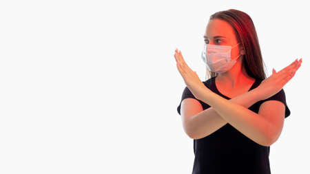 Stop sign. Stay home. Woman in protective mask red glow crossing hands looking aside isolated on white copy space. Forbidden gesture. Quarantine measures. Pandemic restriction. New normal Stock fotó - 155432744