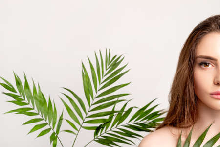 Beauty care. Natural cosmetology. Half face portrait of sensual woman with smooth perfect skin bare shoulder in green exotic palm leaves isolated on light copy space background. Detox therapy. Archivio Fotografico