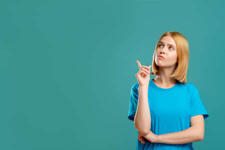 Inspired woman portrait. Answer solution. Pensive blonde lady in blue t-shirt looking pointing at empty space for text isolated on teal promotional background. Insight idea.