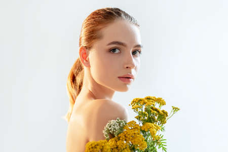 Natural skincare. Herbal therapy. Portrait of sensual woman with perfect face nude makeup bare shoulders wild flowers isolated on light white copy space background. Organic cosmetology.