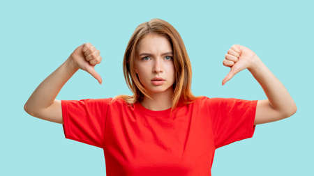 Dislike sign. Disagreement gesture. Portrait of disturbed lady in red t-shirt protesting with thumbs down isolated on blue background. Negative reaction. Blame criticizing. Stock fotó - 155432965