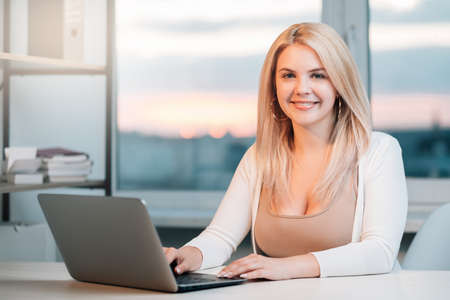 Business webinar. Virtual corporate meeting. Cheerful confident female CEO working with laptop at light cosy home office looking at camera. Video conference. COVID-19 quarantine. Social distancing.
