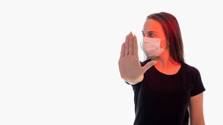 Stop gesture. Social distancing. Woman in protective mask red glow showing forbidden hand looking aside isolated on white copy space. Quarantine measures. Stay safe. Advertising background Stock fotó - 155433143