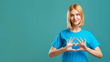 Supportive woman. Love care. Cheerful lady in blue t-shirt showing heart gesture isolated on teal copy space advertising background. Romantic message. Admiration affection. Stock fotó