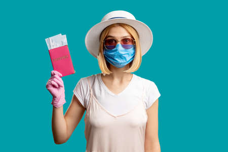 Pandemic prevention. Travel restriction. Woman in summer outfit protective mask pink gloves holding foreign id with tickets. Looking at camera isolated on blue. Quarantine measures. Holiday trip