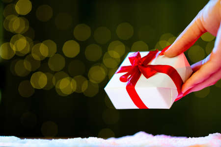 Christmas gift. Holiday surprise. Greeting congratulation. Female hand putting present box taped red ribbon on snowy decor shimmering green blur lights background copy space. Zdjęcie Seryjne