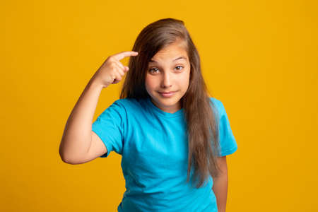 Think use your brain. Smart child. Creative idea. Memory knowledge. Portrait of sarcastic young girl in blue t-shirt pointing finger at temple looking at camera isolated on orange background. Banque d'images