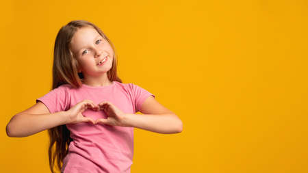 Love sign. Supportive child. Affection sympathy. Compassion encouragement. Cheerful young girl in pink showing heart gesture smiling isolated on orange copy space background.