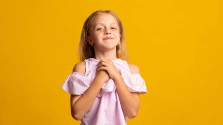 Girl dream. Affection admiration. Compassion love. Portrait of happy satisfied young female kid in pink expecting greeting smiling isolated on orange copy space background.