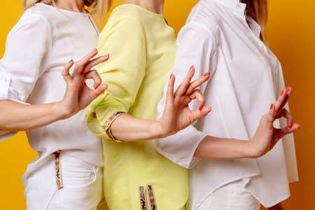 Female approval. OK sign. Acceptance solidarity. Perfect choice. Three women in white yellow blouse supporting idea with hand yes gesture isolated on orange background.